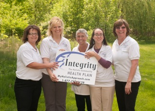 Callard-Moore (second from left) and associates hold up a sign for their holistic healthcare company, Integrity.