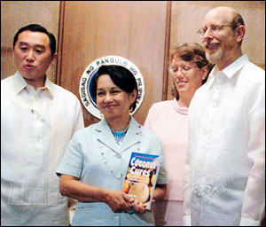 Dr. Bruce Fife presents a copy of his book 'Coconut Cures' to Philippine president Gloria Macapagal-Arroyo. Fife was honored for helping to revive the vital coconut industry in the country.