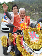 An Okinawan man joins a parade on his motorcycle as part of a celebration of his 96th birthday.